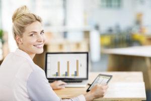 Rear view portrait of female entrepreneur using digital tablet and laptop at desk in office. Horizontal shot.
